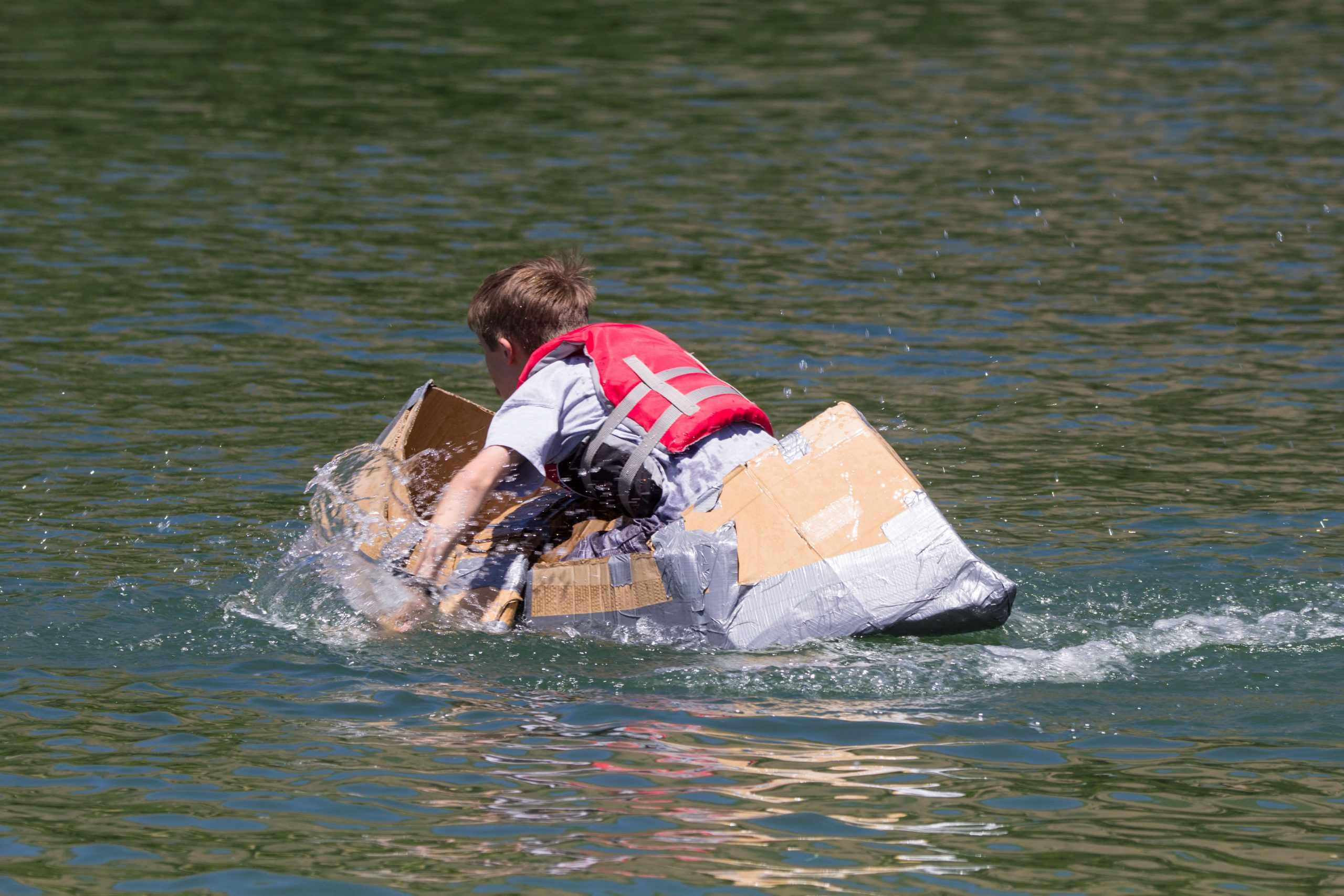 a Boy Paddling a Boat Made of Cardboard